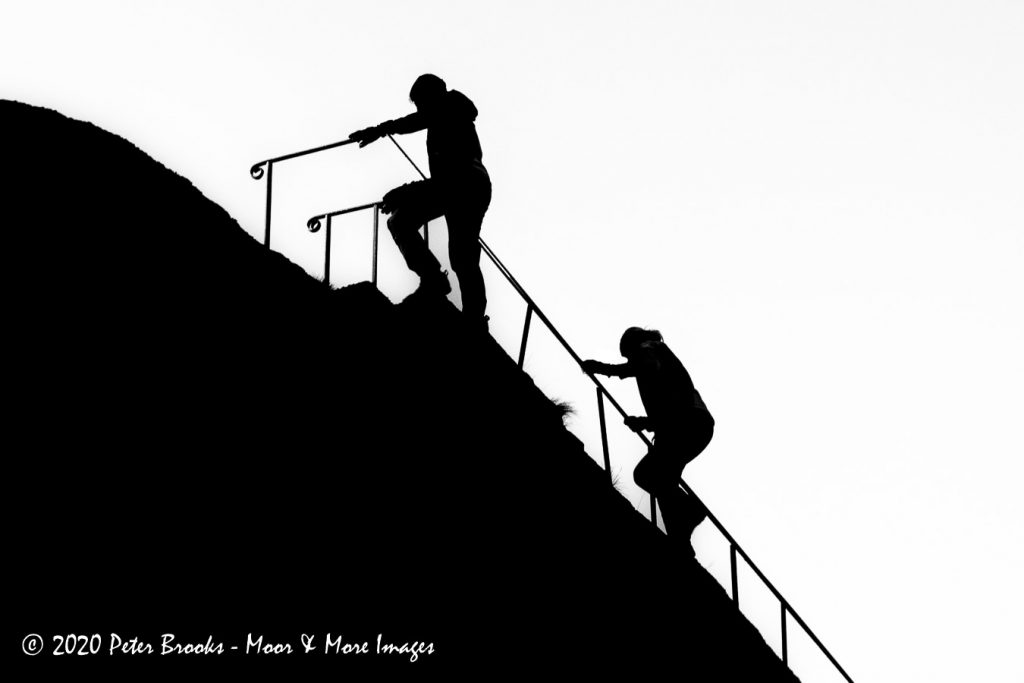 Image of walkers climbing Blackingstone Rock in the style of a linocut.